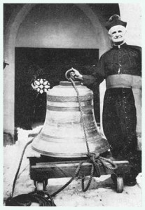 Fr. Timothy Dugan and the bell donated by the Feriola family.